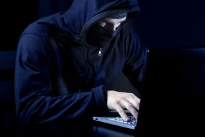 hacker in black with mask using laptop computer