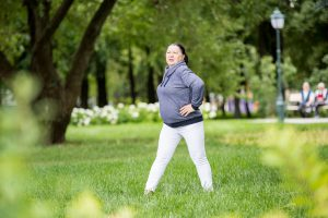 Senior woman doing exercises in green beautiful park. Healthy lifestyle